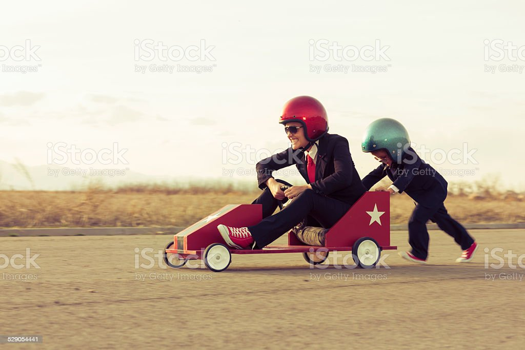 Young Boy with Businesswoman Racing a Toy Car stock photo