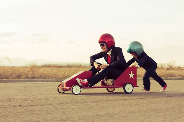 Junge mit Geschäftsfrau-Rennen ein Spielzeugauto – Foto