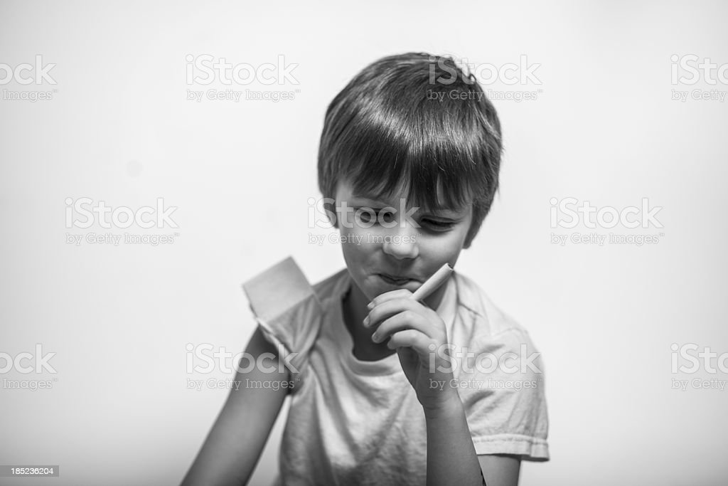 Young Boy with Cigarette in Hand, Black and White royalty-free stock photo