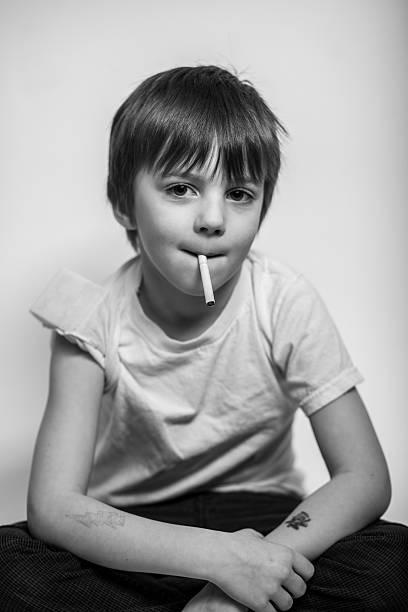 junge junge mit zigarette in hand, tattoo auf arm - lungenkrebs tattoos stock-fotos und bilder
