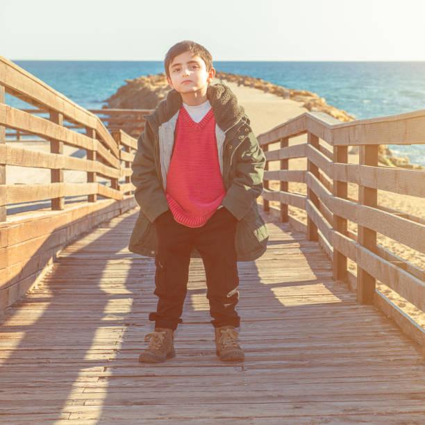 kleiner Junge mit Mantel am Meer – Foto