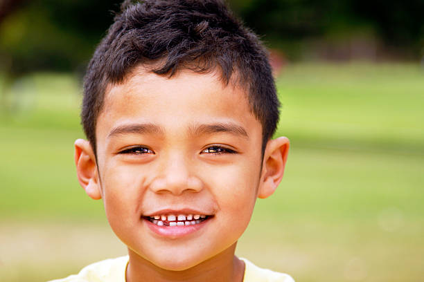 Young boy with dark hair and a missing tooth stock photo