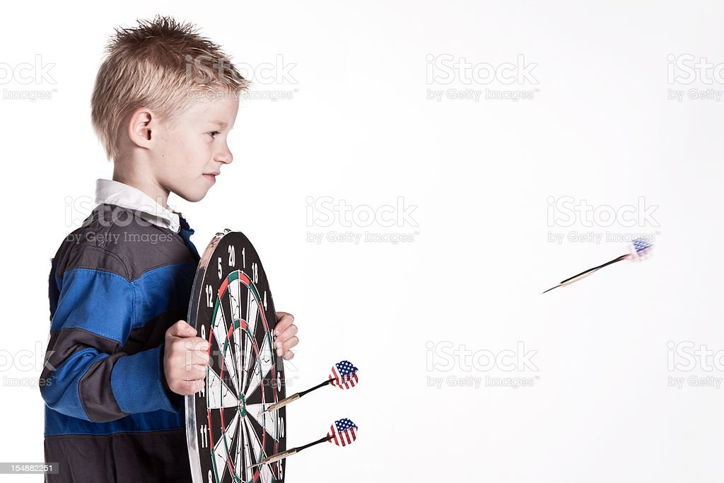 Young boy with dartboard looking an US dart royalty-free stock photo