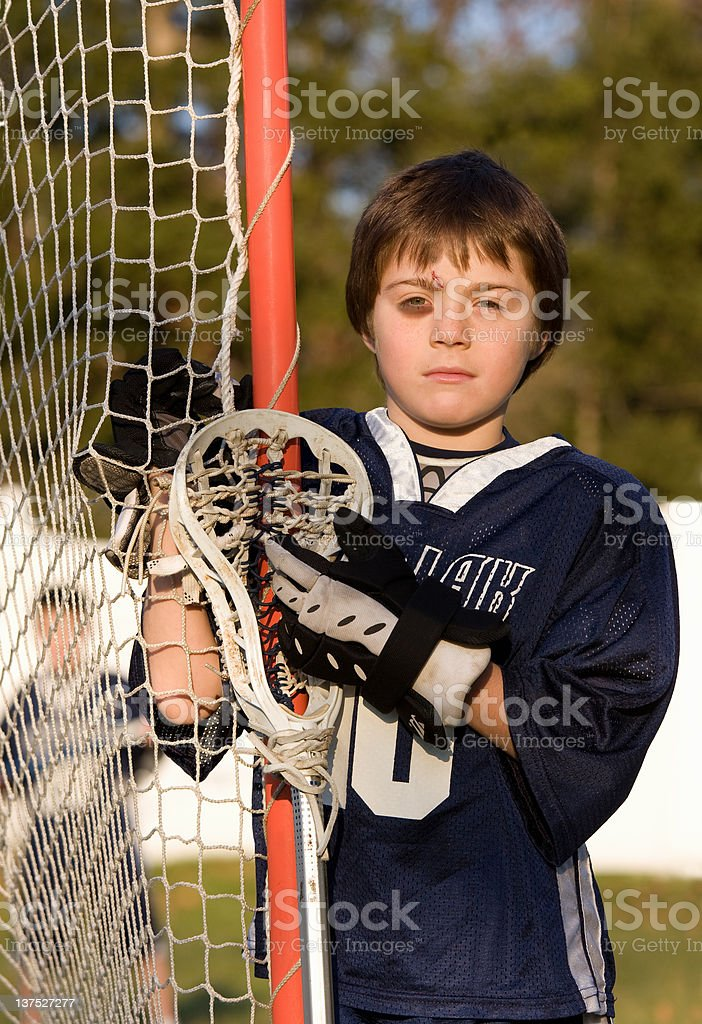 young boy with eye and head injury in lacrosse gear stock photo