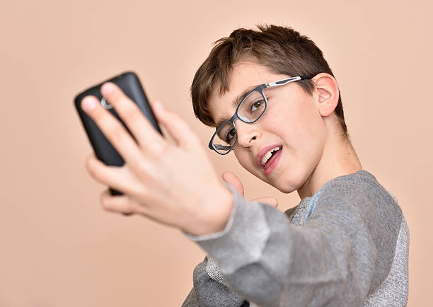 Young boy with glasses taking selfie stock photo