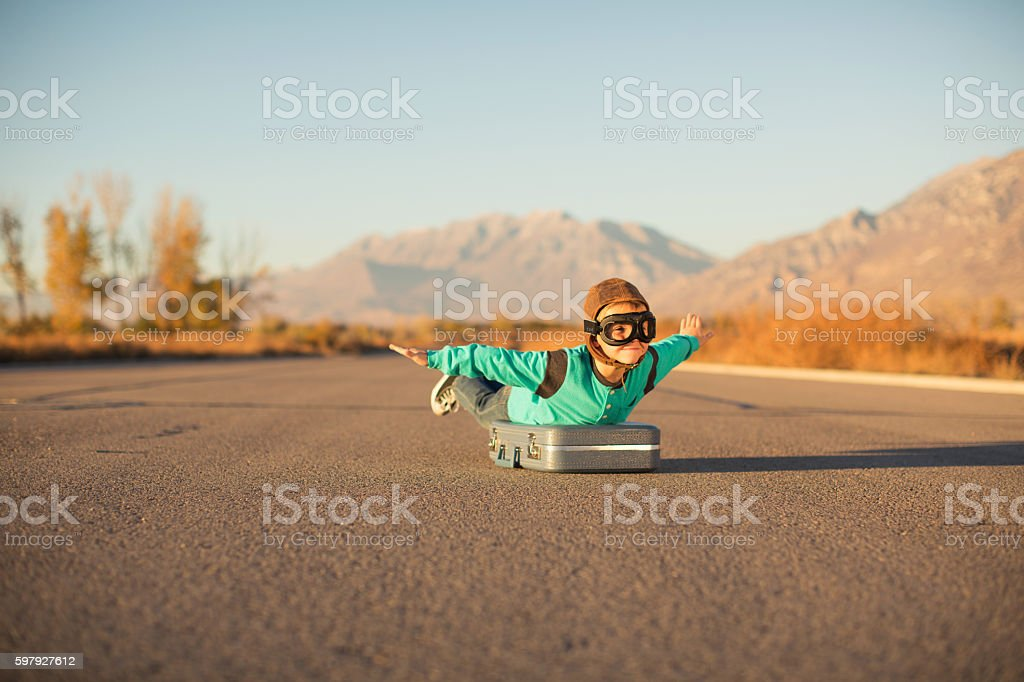 Young Boy with Goggles Imagines Flying on Suitcase stock photo