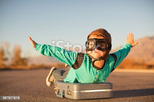 istock Young Boy with Goggles Imagines Flying on Suitcase 597927618