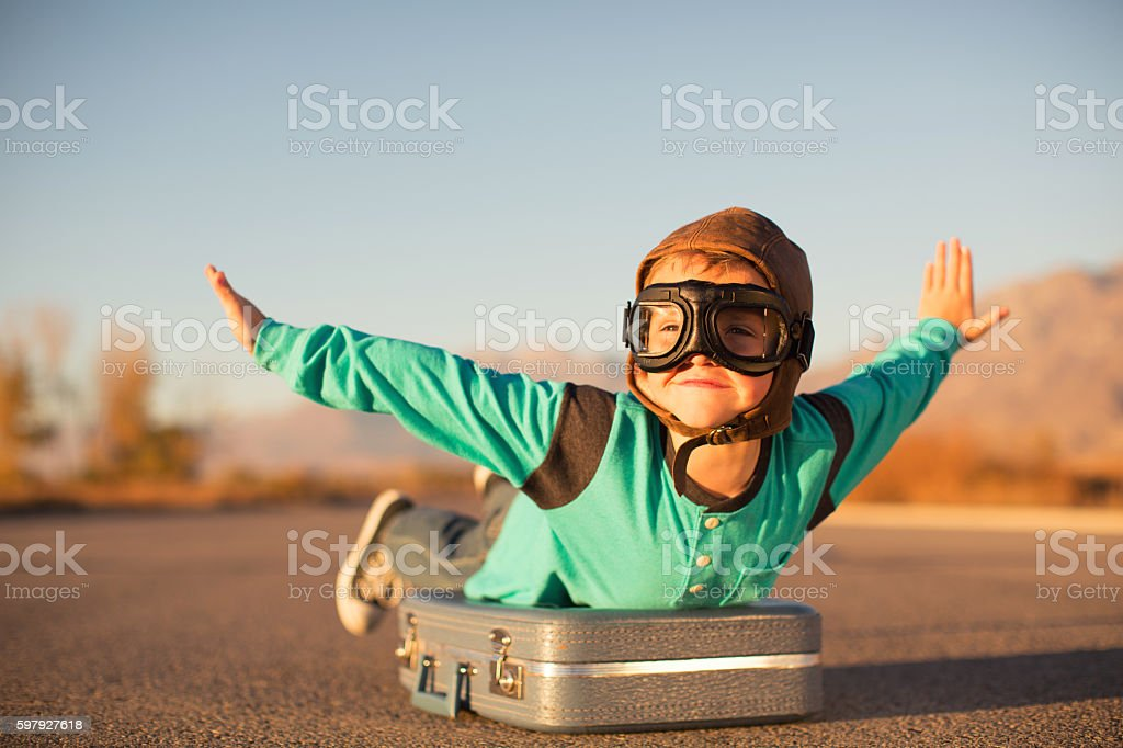 Young Boy with Goggles Imagines Flying on Suitcase stok fotoğrafı