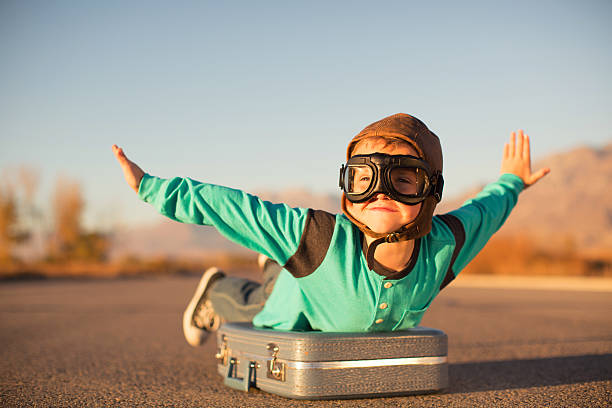 young boy with goggles imagines flying on suitcase - abheben aktivität stock-fotos und bilder