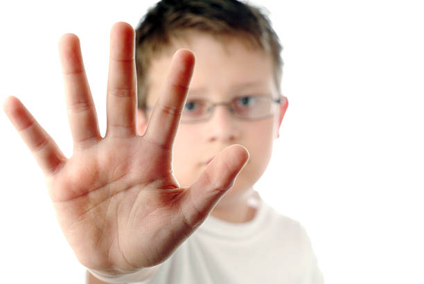 Young Boy with His Arm Stretched Out Saying Stop