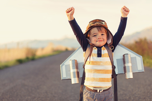A young male child is standing on a rural Utah road wearing a jet pack, flight cap and flying goggles. He wants to be a pilot when he grows up. He is smiling and is raising his arms. He loves aviation.