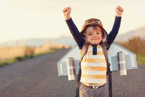 Young Boy with Jet Pack with Arms Raised stock photo