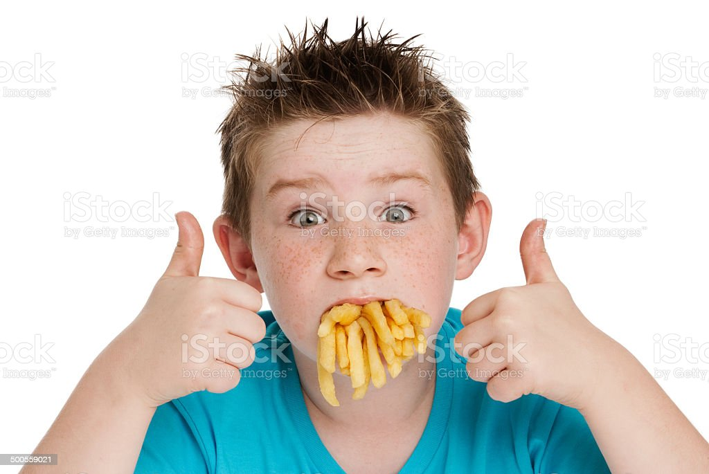 Young Boy with Mouth Full of Chips stock photo