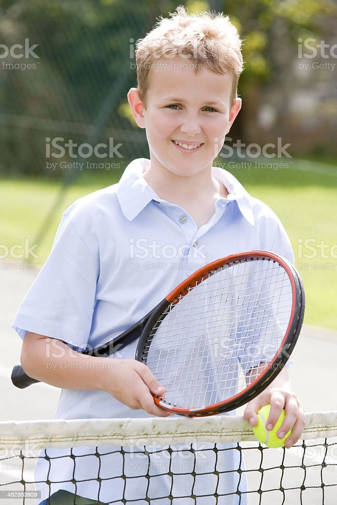 Young boy with racket on tennis court smiling royalty-free stock photo
