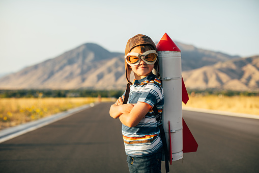 A young boy wearing flying goggles has a rocket strapped to his back as he is ready to fly to new imaginary places. Image taken in Utah, USA.