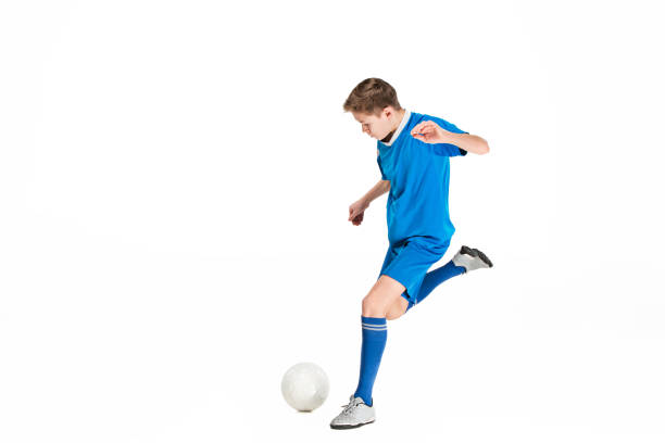 Young boy with soccer ball doing flying kick stock photo