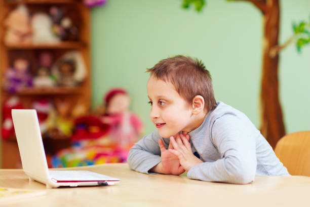 young boy with special needs watching media through the laptop - foto stock