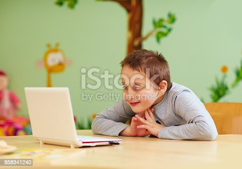 istock young boy with special needs watching media through the laptop 858341240