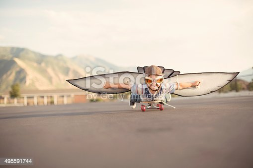 istock Young Boy with Wings Flies On Skateboard 495591744