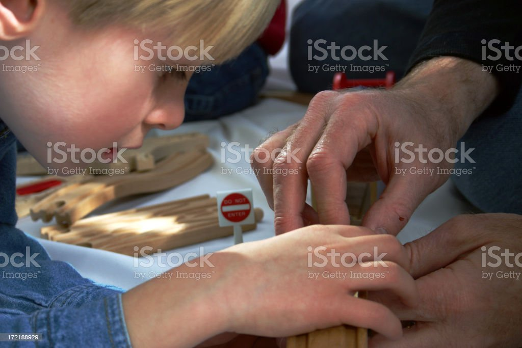 A young boy working closely with a man royalty-free stock photo
