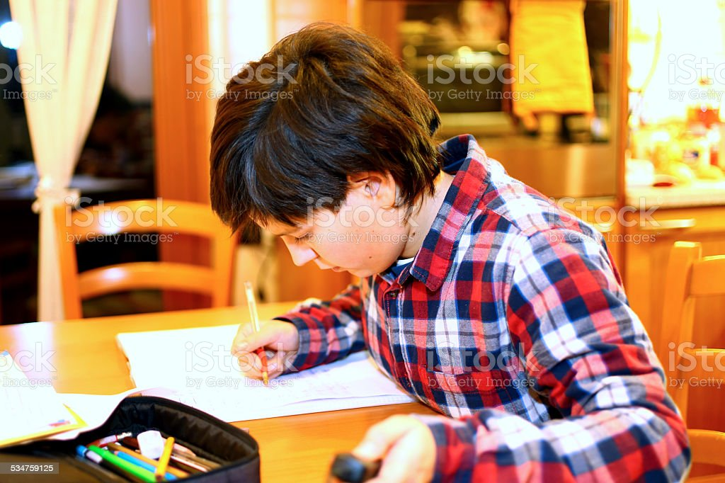 young boy writes on his notebook stock photo