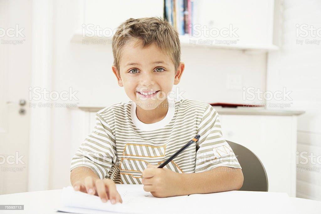 Um jovem rapaz escrito em uma mesa a sorrir foto de stock royalty-free
