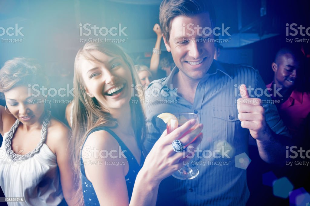 Young boys and girls dancing while enjoying at pub stock photo