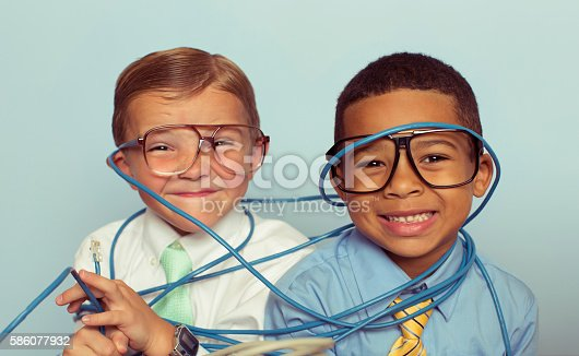 Two young business boys and IT professionals proudly smile through large pile of tangled internet cables on their desk. They are dressed in a dress shirts, ties and glasses while smiling in front of light blue backround. Retro styling. These IT technicians can solve any network problem, even when tangled up.