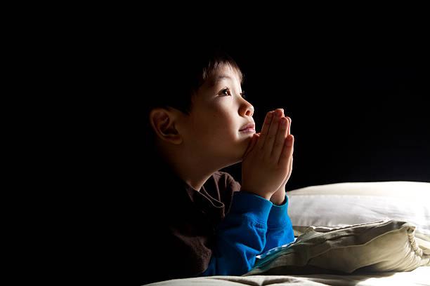 Young boy's bedtime prayer. stock photo