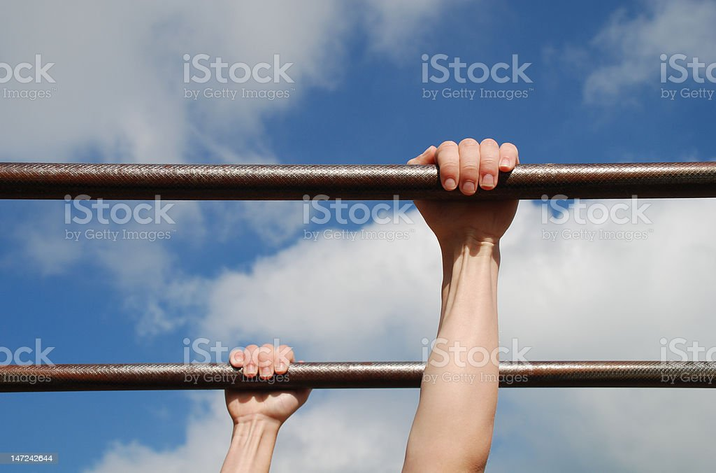 Young Boys Hands on Monkey Bars Young boys' hands gripping monkey bars at an outdoor playground with a blue sky and clouds as a background. Activity Stock Photo