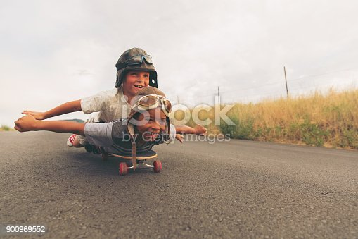 Two young boys dressed in flight caps and goggles ride down a hill on their skateboard hoping to take flight. Their imaginations of being pilots and piloting an aircraft are not too far off. Image taken in Utah, USA.