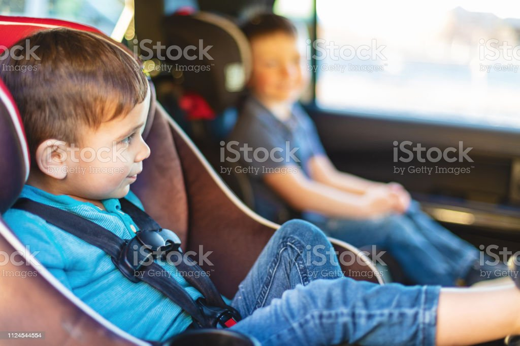 Young Boys in Car Seats Involving Two Parent Family with Mixed Race Adopted Children Safe Driving Preparation for Travel stock photo