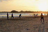 istock Young boys playing cricket game on a beach 929925876