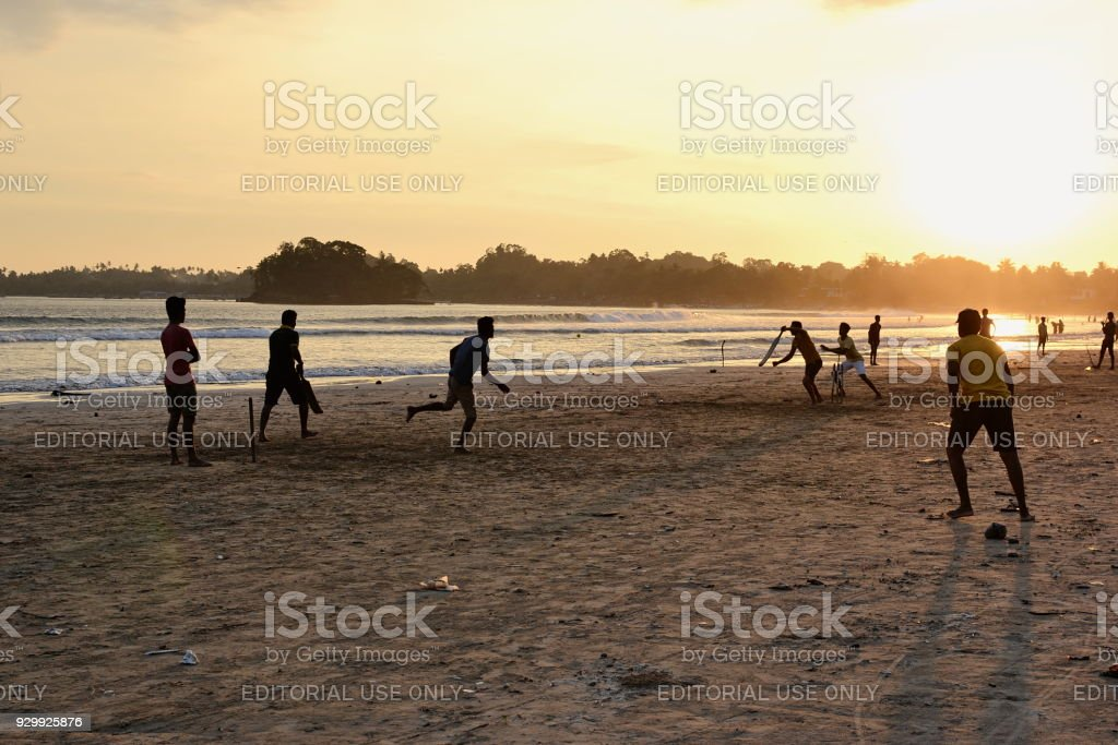 Young boys playing cricket game on a beach stock photo