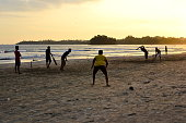 istock Young boys playing cricket game on a beach 929925892