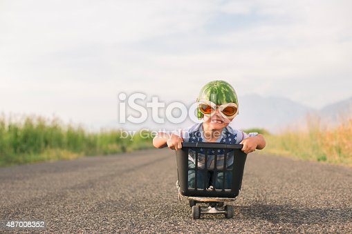 A young boy races his makeshift go-cart while wearing watermelon helmet and goggles. The boy loves speed and smiles as he races down a road.