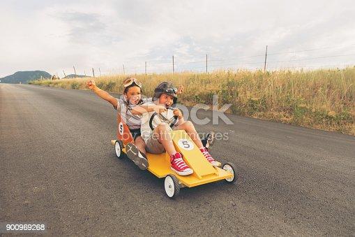 959599892 istock photo Young Boys Racing Homemade Car 900969268