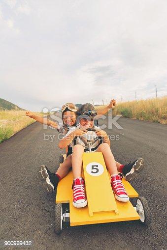 959599892 istock photo Young Boys Racing Homemade Car 900969432