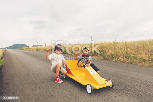 959599892 istock photo Young Boys Racing Homemade Car 900969550