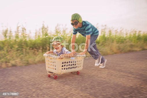A young boy races his brother in a makeshift go-cart while wearing watermelon helmets and goggles. The two boys smile as they love to be living a life full of adventure.
