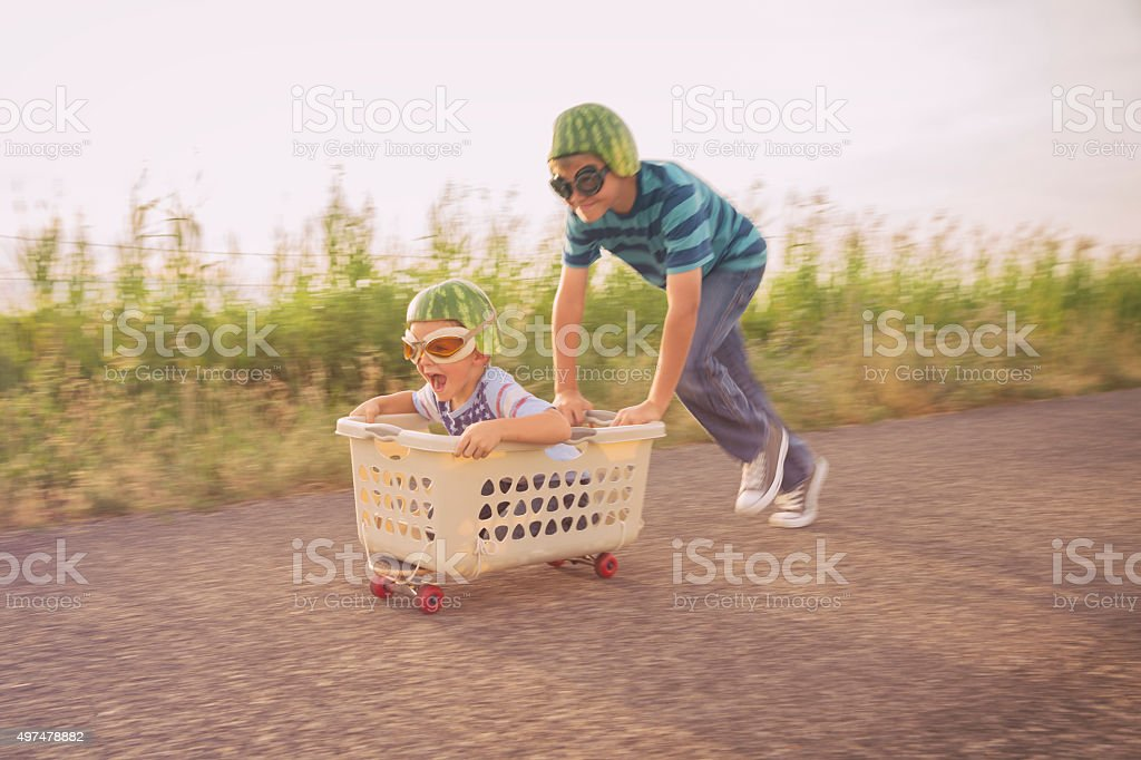 Young Boys Racing on Skateboard Wearing Watermelon Helmets stock photo