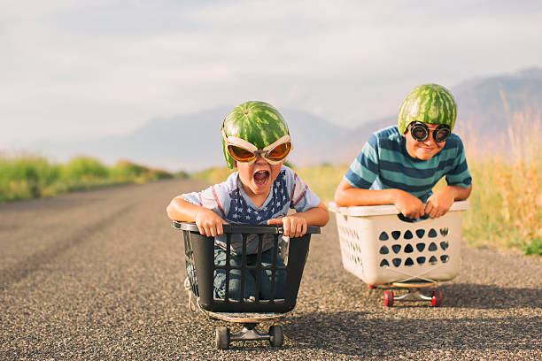 young boys racing wearing watermelon helmets - humor stock photos and pictures