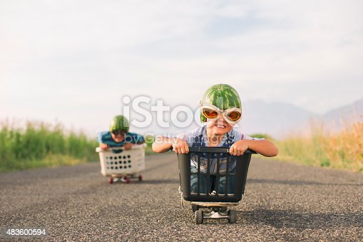 A young boy races his brother in a makeshift go-cart while wearing watermelon helmets and goggles. He is excited as he is winning the race.