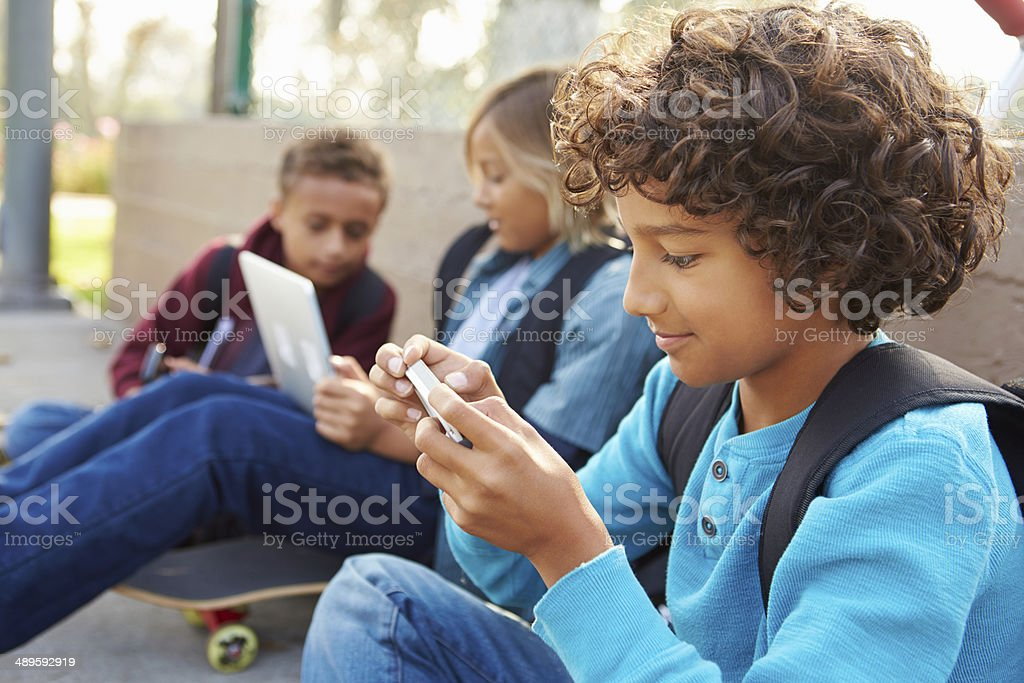 Young Boys Using Digital Tablets And Mobile Phones In Park stock photo