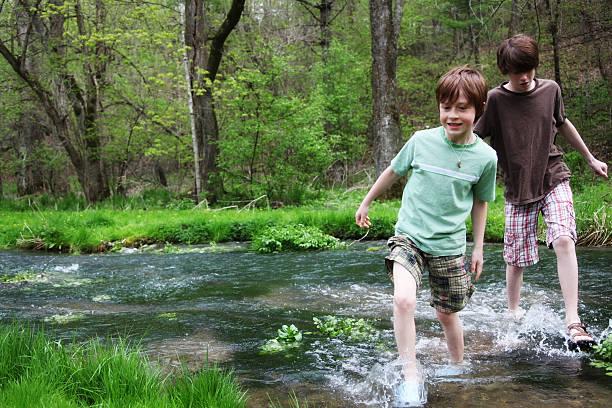 young boys wading through a stream flowing across a forest - bos spelen stockfoto's en -beelden