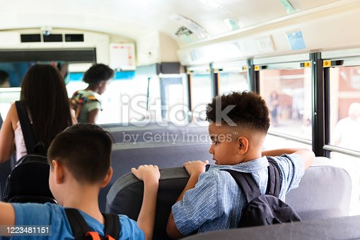 1031397608 istock photo Young boys wait to get off school bus 1223481151