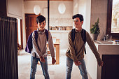 Teenage brothers with backpacks returning home from school and doing the floss dance