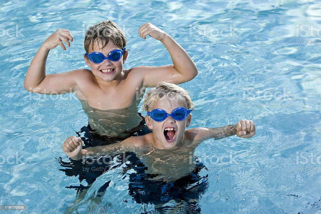 Young boys with goggles playing in a swimming pool royalty-free stock photo