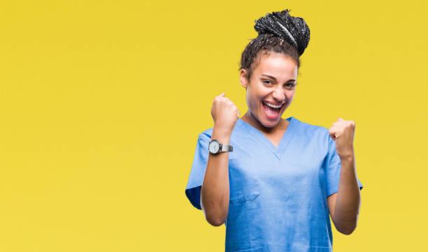 年輕編織頭髮非洲裔美國女孩專業護士在孤立的背景非常高興和興奮做優勝者手勢與手臂抬起, 微笑著尖叫成功。慶祝理念。 - 欣喜若狂 個照片及圖片檔