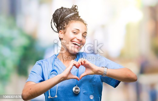 Young braided hair african american girl professional surgeon over isolated background smiling in love showing heart symbol and shape with hands. Romantic concept.